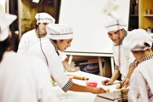 This picture shows several chefs preparing food together in a kitchen.