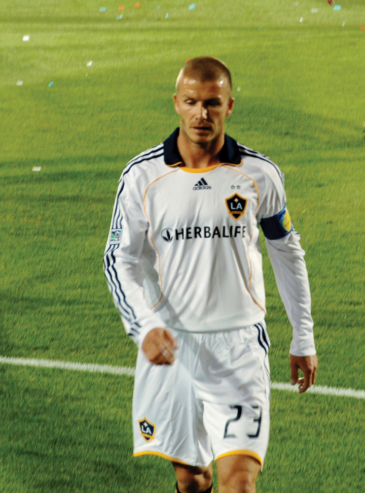 This picture shows David Beckham walking across a playing field in an L.A. Galaxy team jersey.