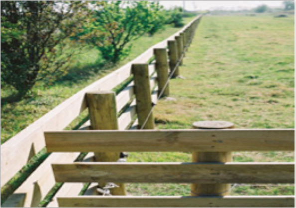 This picture shows a fenceline that continues out of focus down the length of a field.