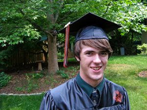 This picture shows a smiling young man wearing a graduation cap and gown.