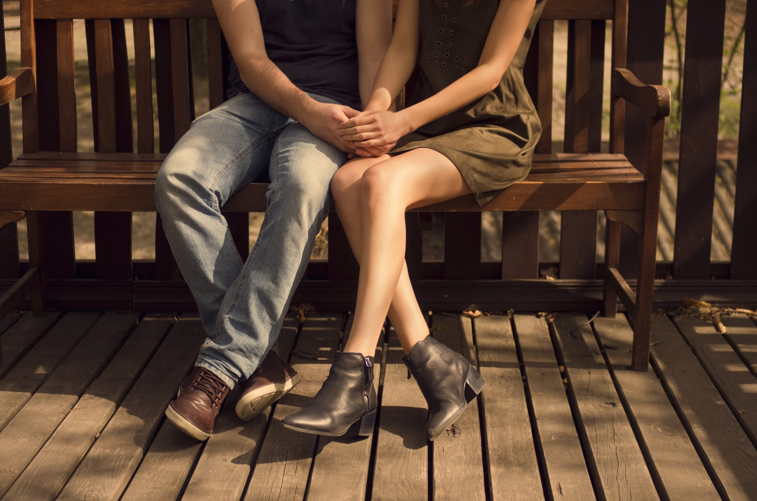 This picture shows a young couple holding hands while seated on a bench.