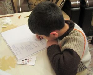This picture shows a young boy writing a test.