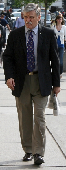 This picture shows Roméo Dallaire walking on the sidewalk on a busy city street.