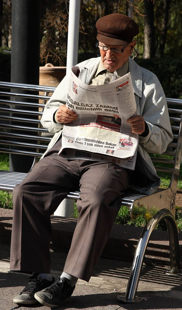 This picture shows a man reading a newspaper while seated on a park bench.