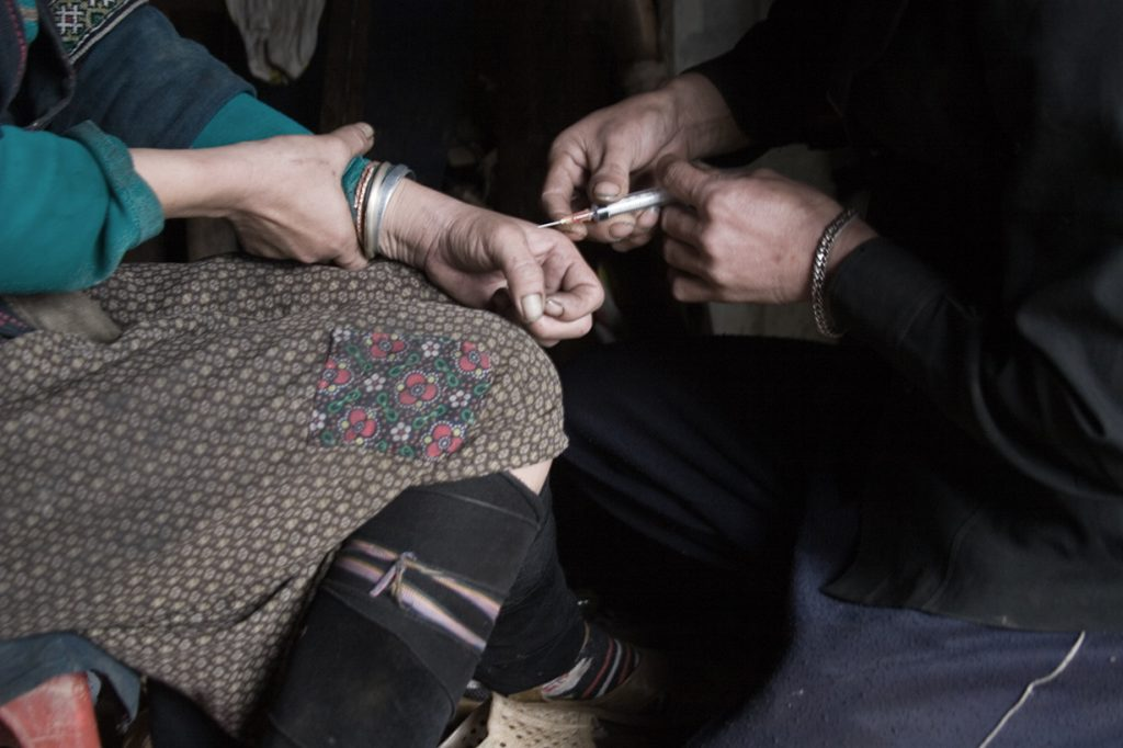 This picture shows a woman being injected in the hand with a syringe.