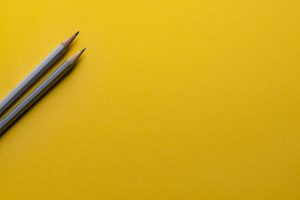 This picture shows two grey pencils with a yellow background.