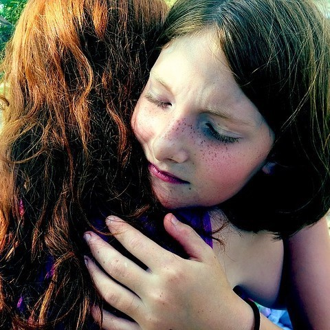 This picture shows a young girl with eyes closed hugging her friend.