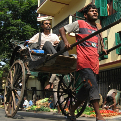 This picture shows a rickshaw driver pulling a passenger down a city street.