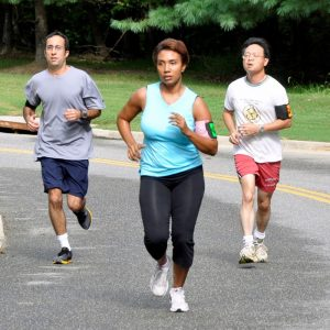 This picture shows a group of joggers running through a park.