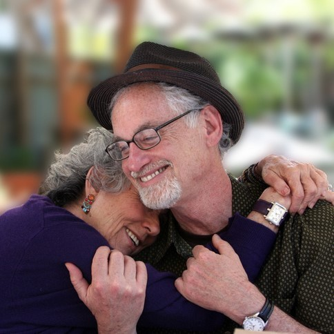 This picture shows a grey-haired couple sharing an affectionate hug.