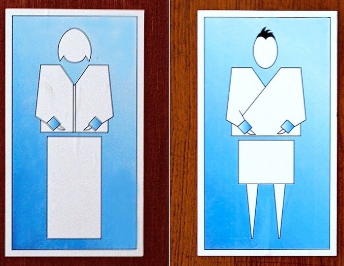 This picture shows restroom signs from the country of Bhutan, displaying stylized representations of a woman and man dressed in traditional clothing.