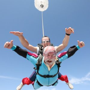 This picture shows an older man with white hair and beard skydiving in tandem with a younger jumpmaster.