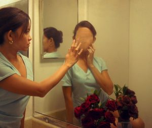 This picture shows a woman looking into the mirror and seeing a faceless reflection.