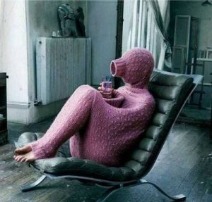 This picture shows a person sitting on a chair almost completely hidden inside a long sweater.