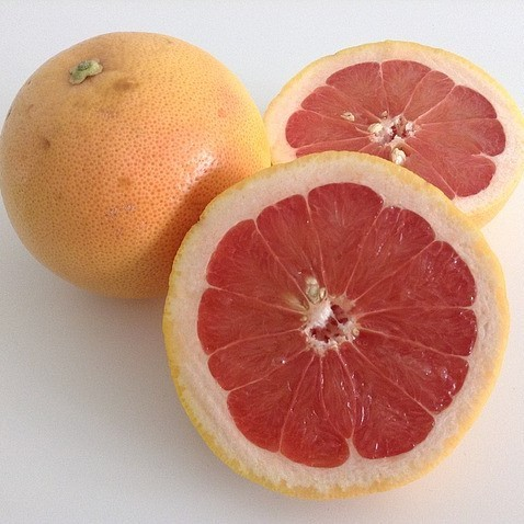 This picture shows two grapefruit, one whole and one cut in half.
