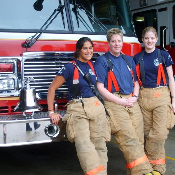 This picture shows three female members of a fire and rescue team stand in front of a fire engine wearing firefighting safety clothing.
