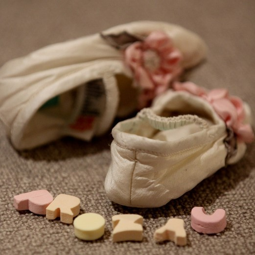 """This picture shows baby shoes and the word """"Prozac"""" spelled out with small, candy-like letters on the floor."""