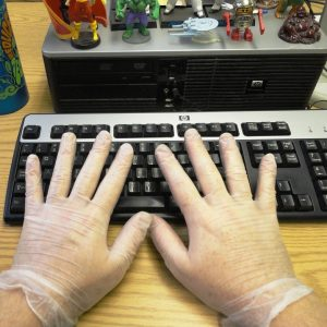This picture shows a man's hands wearing latex gloves while typing on a computer keyboard.
