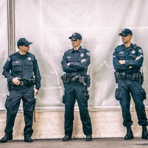 This picture shows a group of uniformed police officers standing together on the sidewalk.