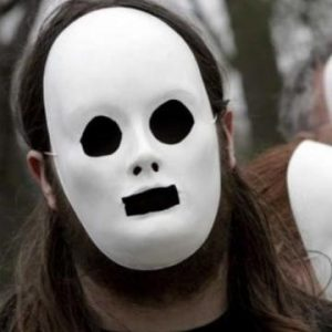 This picture shows a man wearing an expressionless, white plaster mask with black eyes and mouth.