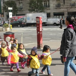 This picture shows a group of preschool students being led along a city street by an adult.