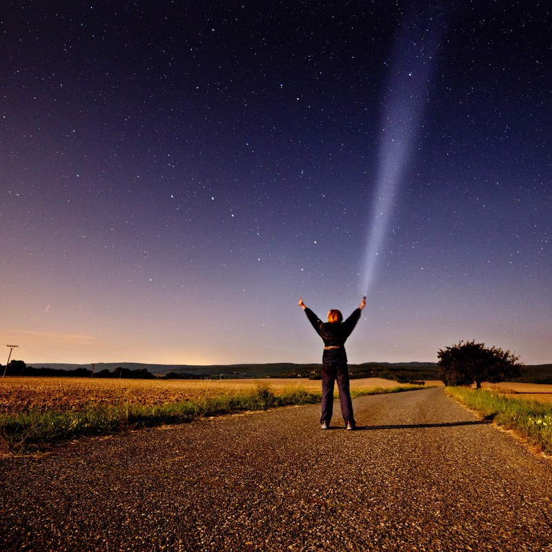 This picture shows a woman standing in the middle of a country road at night and reaching toward the star-filled sky above.