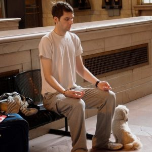 This picture shows a young man meditating on a bench in a train station.