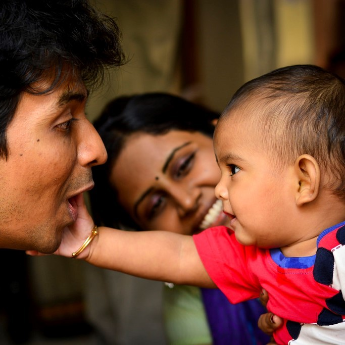 This picture shows a baby reaching out to touch the face of his smiling father as a happy mother looks on.
