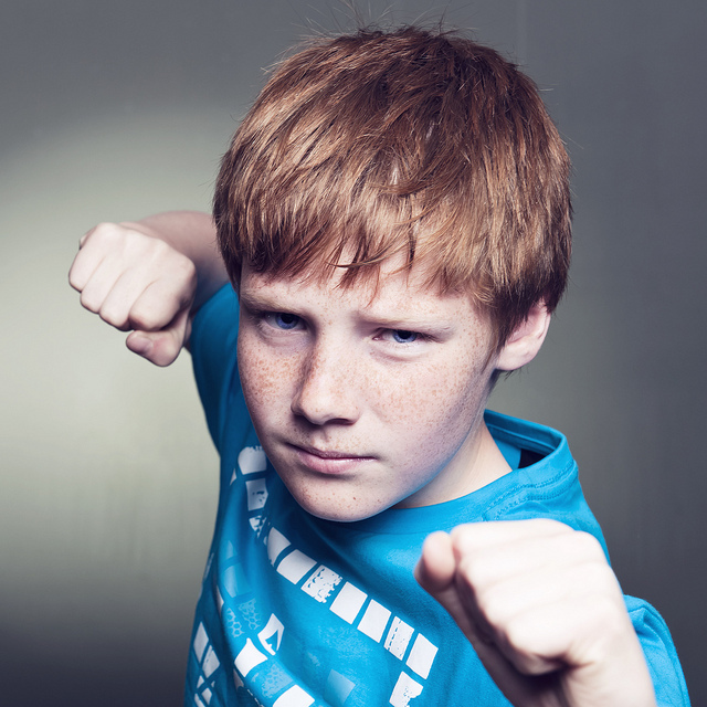 This picture shows a boy raising his fists as if to fight.