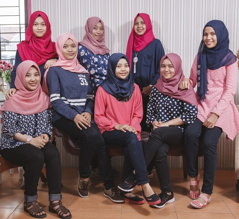 This picture shows a group of Malaysian teen girls posed for a photo wearing casual clothing and traditional head scarves.