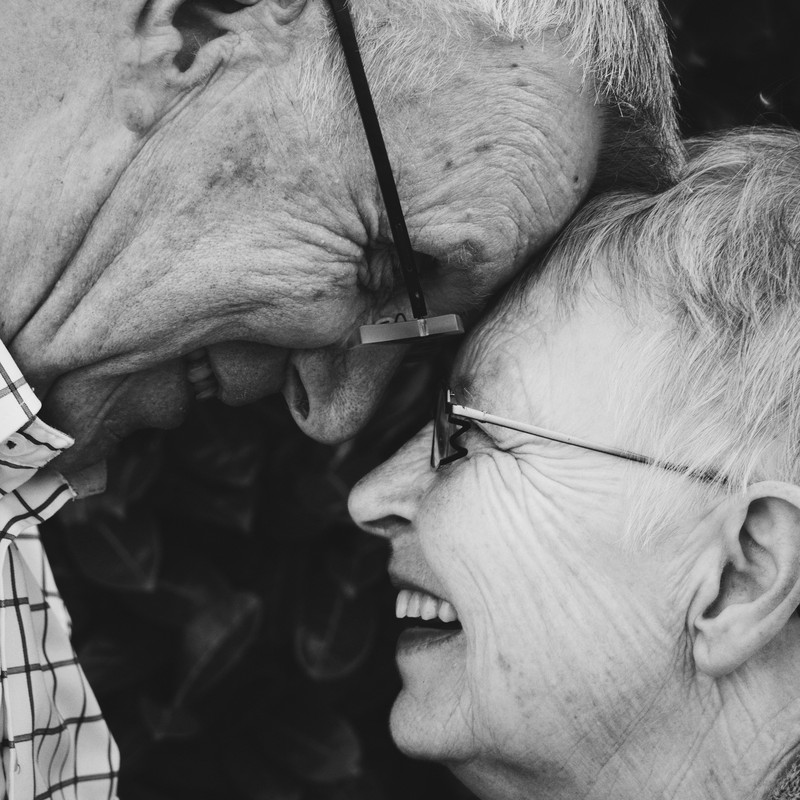 This picture shows a smiling elderly couple looking into each other's eyes while their foreheads touch.