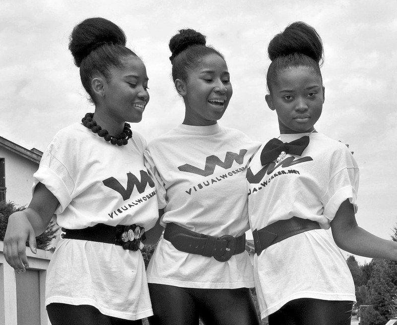 This picture shows a group of teen girls with matching shirts and hairstyles posing together with their arms around one another.