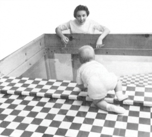 This picture shows a baby crawling to a woman over a surface that is part checkered table cloth and part clear glass.